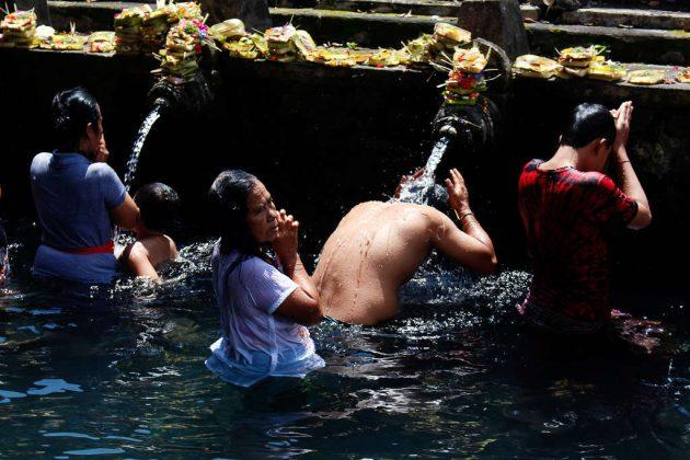 Gente purificándose en el templo Tirta Empul (Bali, Indonesia)